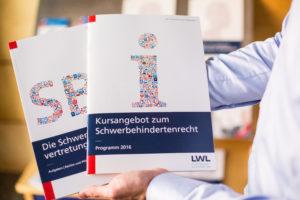 Ein Mitarbeiter des LWL-Integrationsamtes zeigt zwei Hefte aus der Infothek, unter anderem das Kursangebot des Amtes zum Schwerbehindertenrecht.