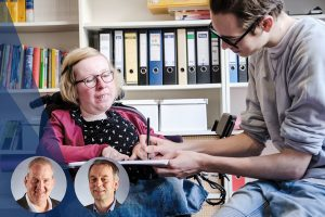 Eine Frau mit Rollstuhl und ein Auszubildender mit Lernbehinderung sitzen zusammen über einem Formular und tragen etwas ein.