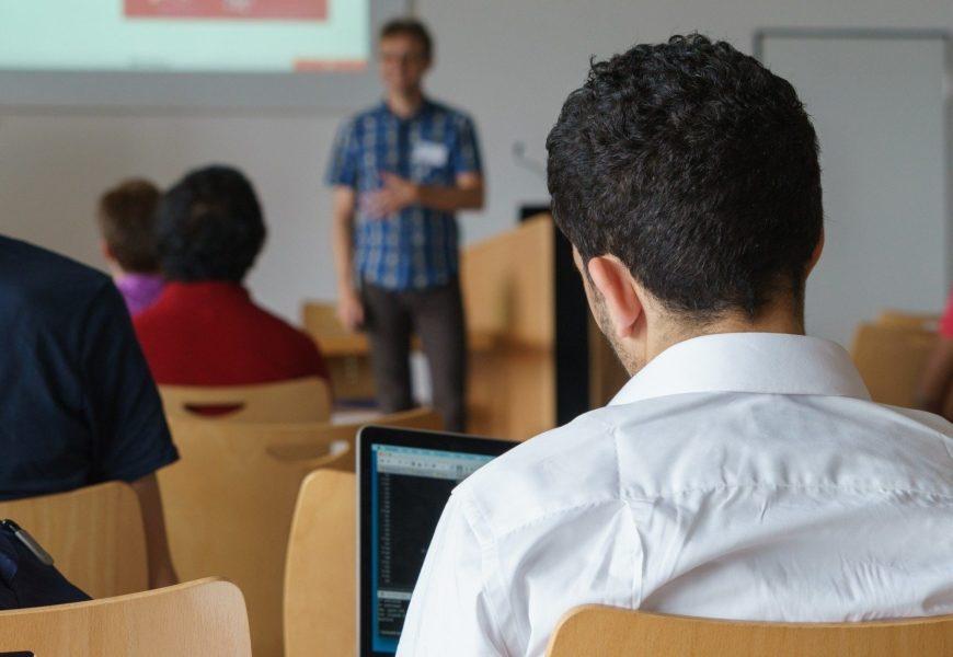 Ein Mann mit dunklem Haar in einem Seminarraum neben anderen Teilnehmern von hinten fotografiert, vorne steht unscharf ein Referent.