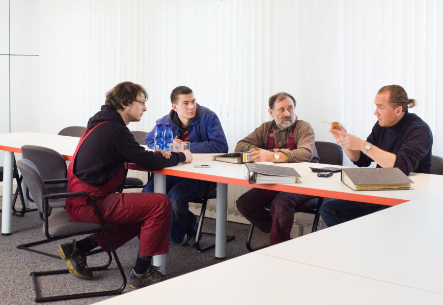 Eine Gruppe Männer in unterschiedlicher Berufskleidung sitzt in einem Tagungssaal an einem Tisch zusammen und unterhält sich.