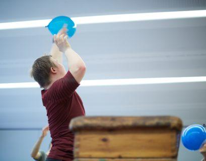 Ein Junge in Sportklamotten in einer Turnhalle mit einem blauen Luftballon in der Hand, fotografiert im Sprung nach oben.