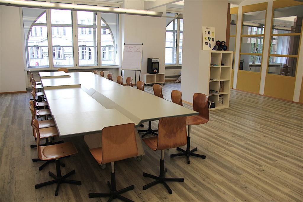 Ein großer, leerer Tisch, dessen Tischplatte verschiedene Höhen hat. Er steht in den Räumen des Coworking-Spaces in Berlin. Drumherum stehen ordentlich viele Stühle.
