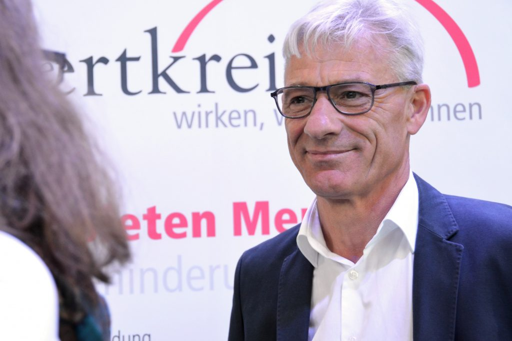 """Ulrich Rötgers, im Hintergrund ein weißes Plakat mit der teilweise lesbaren Aufschrift """"wertkreis""""."""
