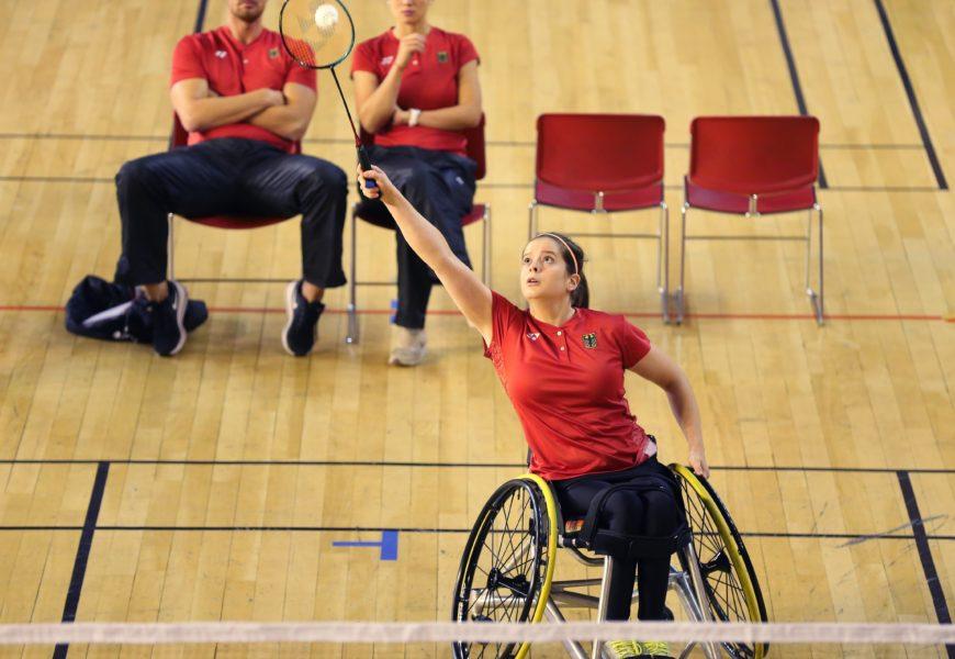 Valeska Knoblauch spielt in rotem Turnier-Trikot Para-Badminton in einer Sporthalle. Sie ist von vorne bei der Ballannahme zu sehen.