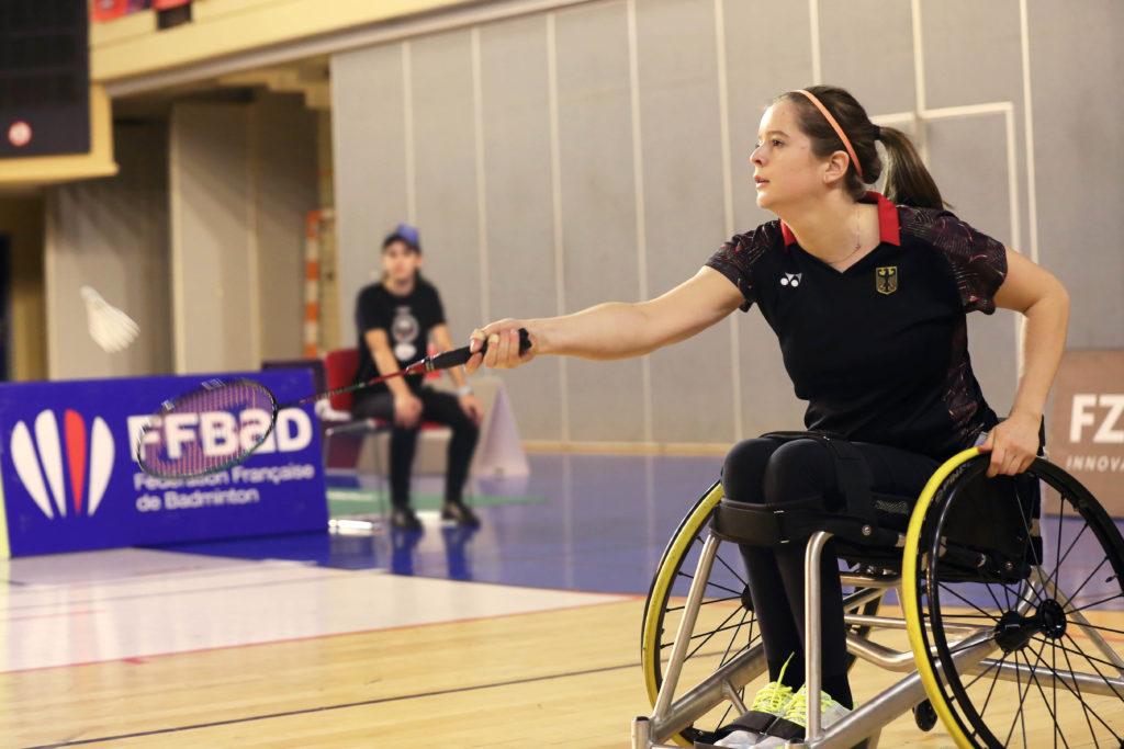 Valeska Knoblauch spielt in schwarzem Trikot Para-Badminton in einer Sporthalle. Sie ist von der Seite bei der Ballannahme zu sehen, im Hintergrund unscharf ein Balljunge am Spielfeldrand.