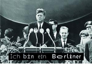 """Der ehemalige Präsident der USA, Kennedy, steht an einem Rednerpult. Darunter ist in WaveFont-Untertiteln der Satz """"Ich bin ein Berliner"""" dargestellt."""