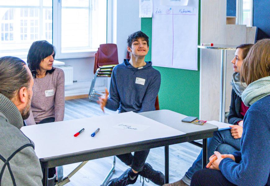 Blick in eine Workshop-Runde, in der mehrere Menschen um einen Tisch herum sitzen. Einer davon hat eine körperliche Behinderung und erklärt auf dem Foto gerade etwas.