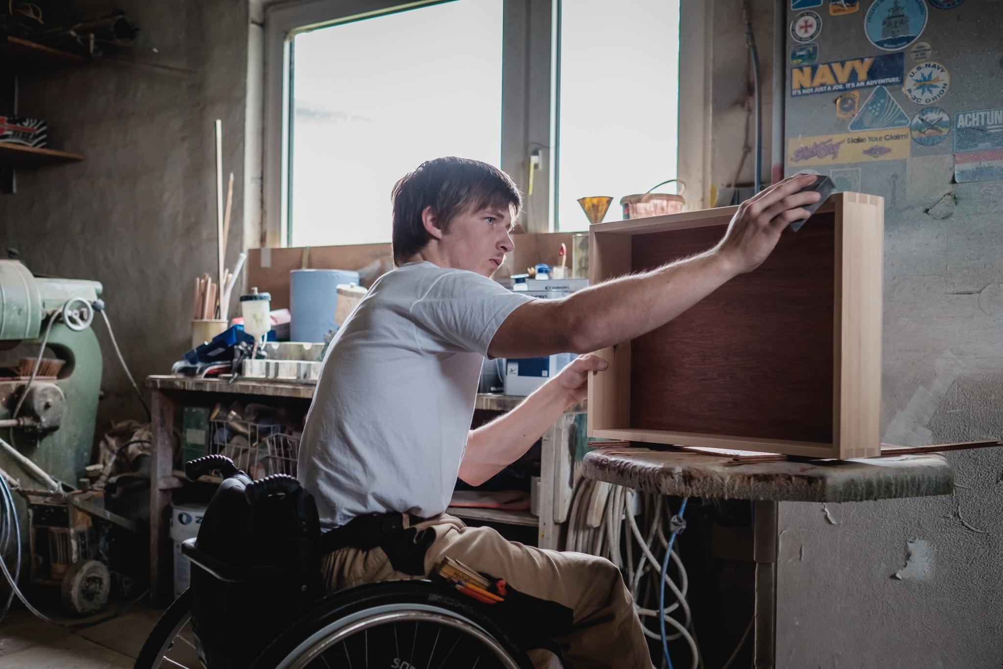 Ein junger Mann mit Rollstuhl sitzt in einer Tischlerwerkstatt und bearbeitet konzentriert eine Holzschublade, vor ihm auf einer Werkbanksteht.