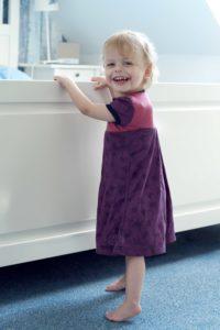 Laura, die zweite Tochter der Brunners, in einem selbstgenähten Kleidchen; sie lacht in die Kamera.