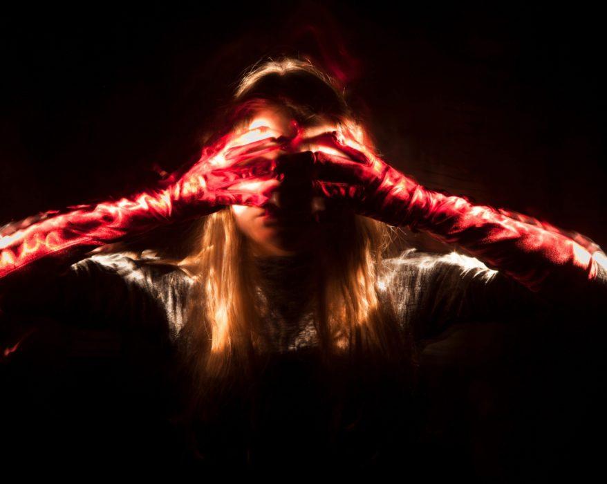 Eine Frau vor tiefschwarzem Hintergrund mit langen Haaren und roten Handschuhen hält sich die Augen zu. Die Handschuhe und die Haare leuchten.