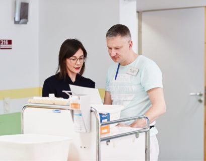 Jobcoachin Marie-Theres Hübner (links) bespricht mit ihrem Klienten Mark Prosser (rechts) ein Dokument, das sie in der Hand hält. Beide stehen in einem hellen Raum vor einem Wagen mit medizinischen Arbeitsmitteln.