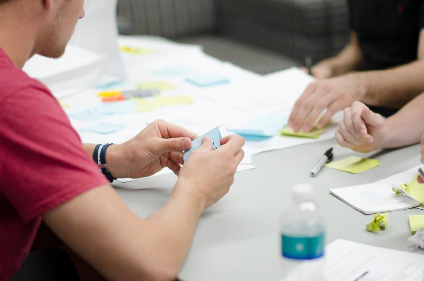 Zwei Personen sitzen sich am Schreibtisch gegenüber und arbeiten zusammen; es sind nur die Hände und Zettel auf dem Tisch zu sehen.