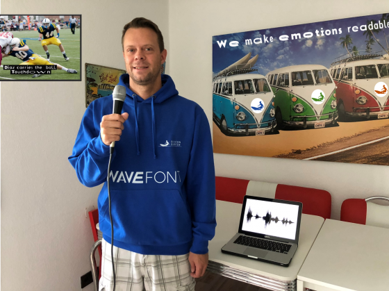 Tim Schlippe steht mit einem Mikrofon in der Hand in seinem Büro neben einem Laptop, kurz bevor er Informationen in das Mikro spricht.