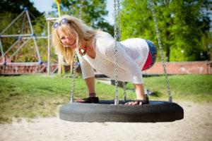 Silke Naun-Bates balanciert auf ihren Händen auf einer großen Reifenschaukel und lacht.
